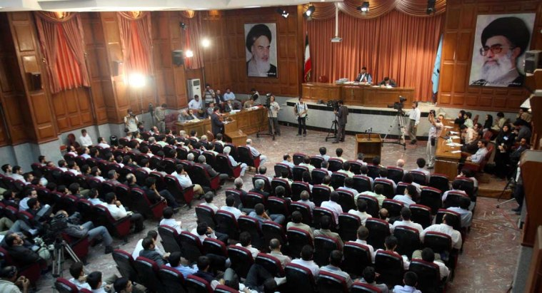 A general view of a courtroom shows suspected opposition supporters (in grey) attending the latest session in their trial at the revolutionary court in Tehran on August 25, 2009. Several aides to former Iranian president Mohammad Khatami and top reformists were put on trial on charges of masterminding the post-election unrest which rocked the Islamic republic. Among the some 20 people in the dock were a former minister and a number of other top political figures as well as journalists and academics. Portraits on the wall show the Islamic republic's supreme leader Ayatollah Ali Khamenei (R) and his predecessor, the late Ayatollah Ruhollah Khomeini. AFP PHOTO/FARS NEWS/HASSAN GHAEDI (Photo credit should read Hassan Ghaedi/AFP/Getty Images)