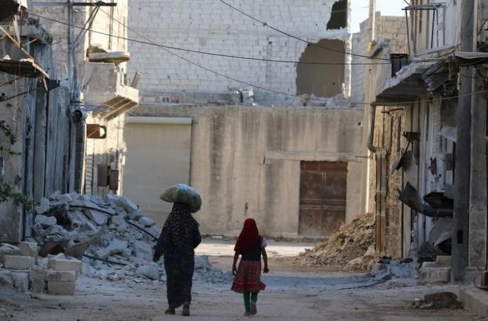 Civilians walk past damaged buildings in the rebel-held al-Sheikh Said neighbourhood of Aleppo